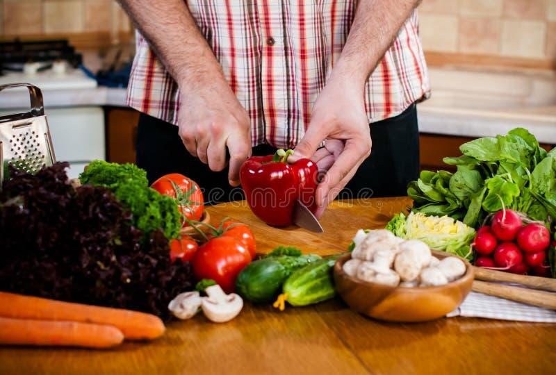 Mannen klipper nya vårgrönsaker arkivbild