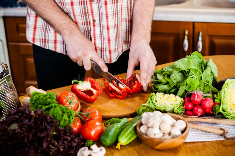 Mannen klipper nya vårgrönsaker royaltyfria foton