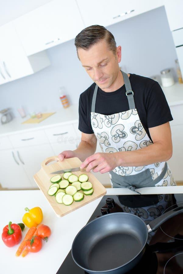 Mannen klipper nya vårgrönsaker på köksbordet arkivfoto