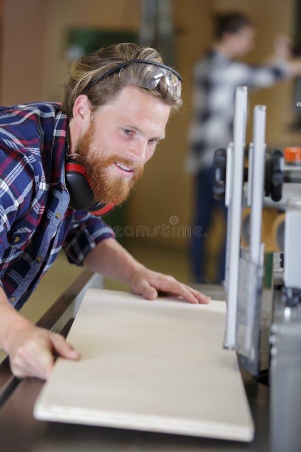 Mannen klipper trä i seminarium arkivbilder