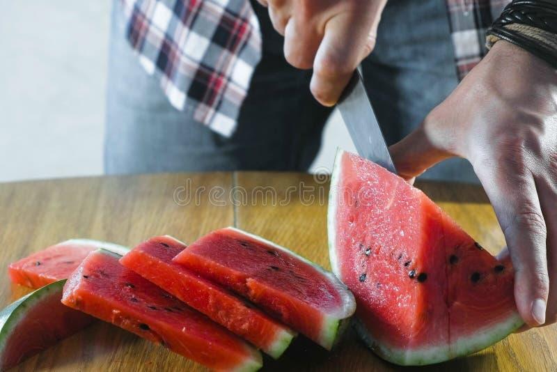 Mannen klipper vattenmelon in i små skivor på köksbordet täta händer upp royaltyfria foton
