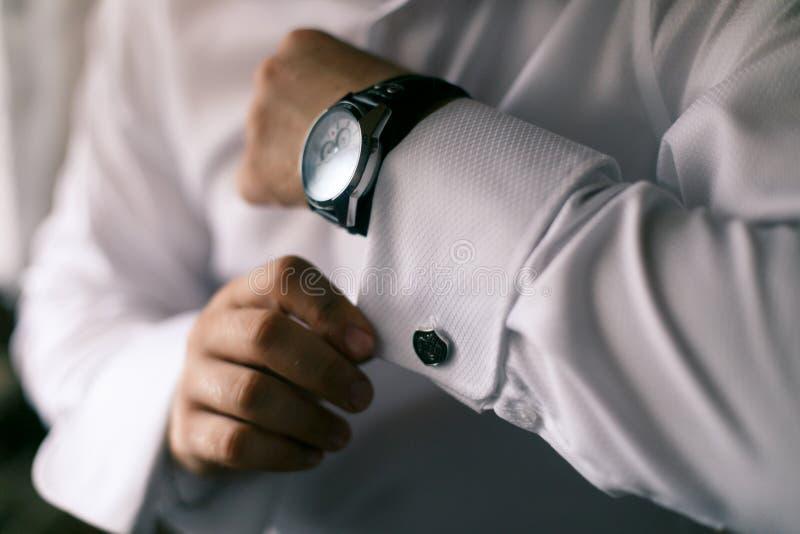 Mannen knäppas på handmanschetterna till klockan royaltyfri fotografi