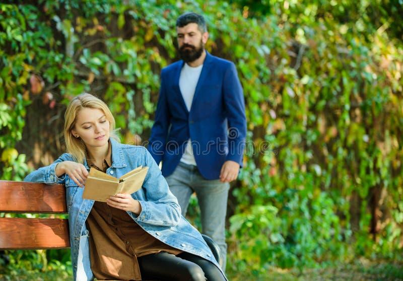Mannen kom till flickvännen på datum Överraskning för henne Flickan sitter bänken lästa boken medan väntanpojkvännen romantiska f royaltyfri foto