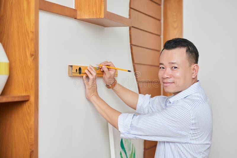 Mannen kontrollerar evennessen av väggen arkivbild