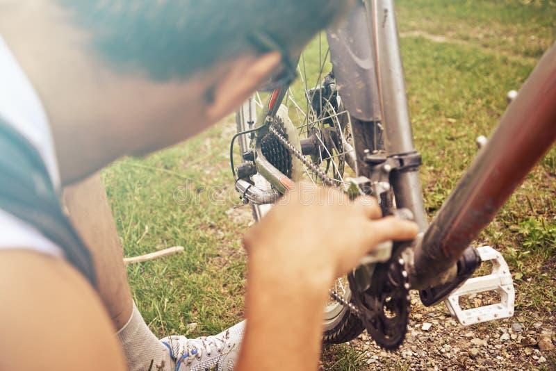Mannen kontrollerar kedjan av cykeln arkivfoto