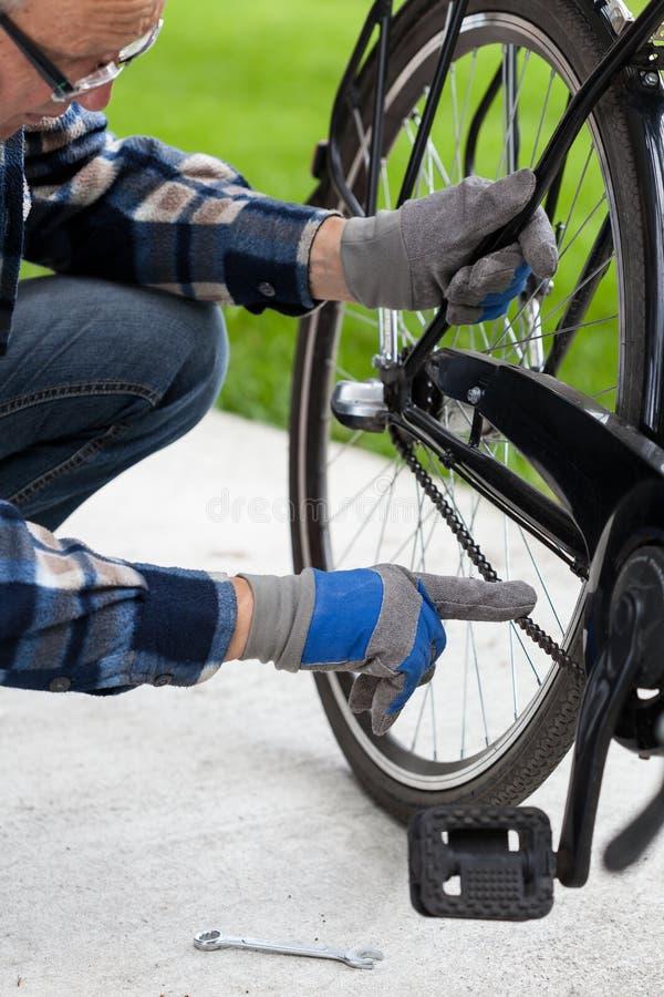Mannen kontrollerar kedjan från cykeln royaltyfri bild