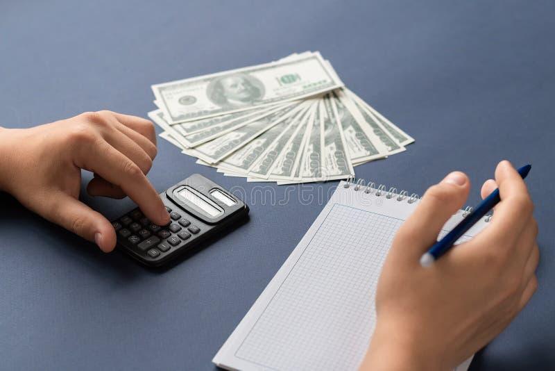 Mannen kopplas in i beräkning av budgeten Maninnehavpenna som ligger bredvid anteckningsboken, räknemaskinen och pengar fotografering för bildbyråer