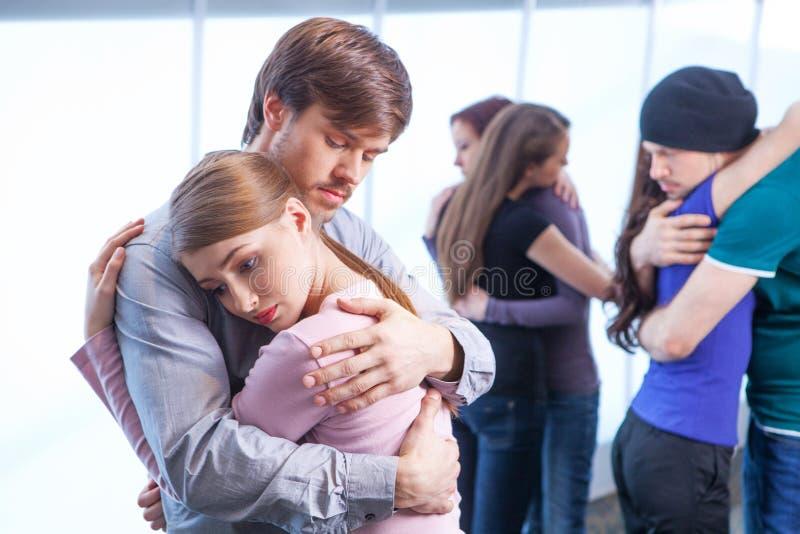 Mannen kramar en kvinna på förgrund. arkivbilder