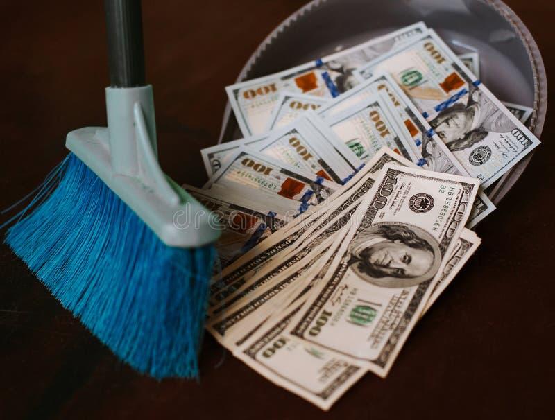 Mannen krattar i pengarna i savok Svep av sedeln i avfallet Rena pengar i avfallet royaltyfri bild