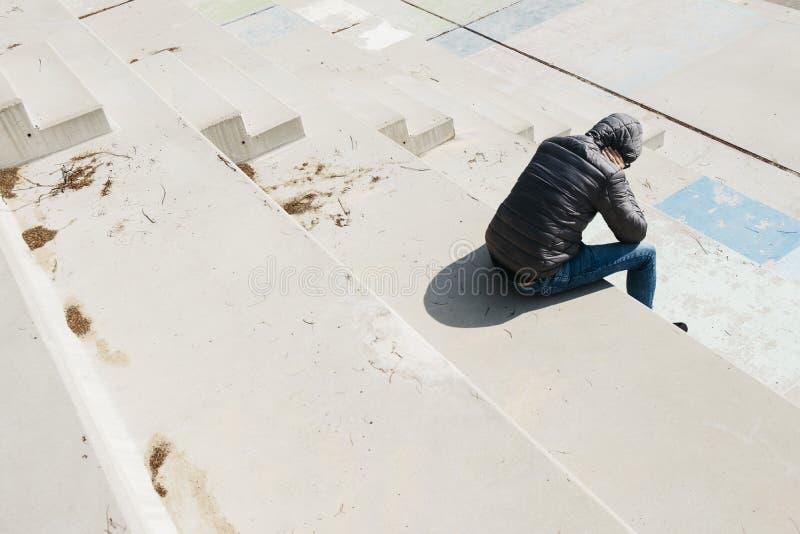 Mannen krullade upp att sitta p? en utomhus- trappa royaltyfri bild