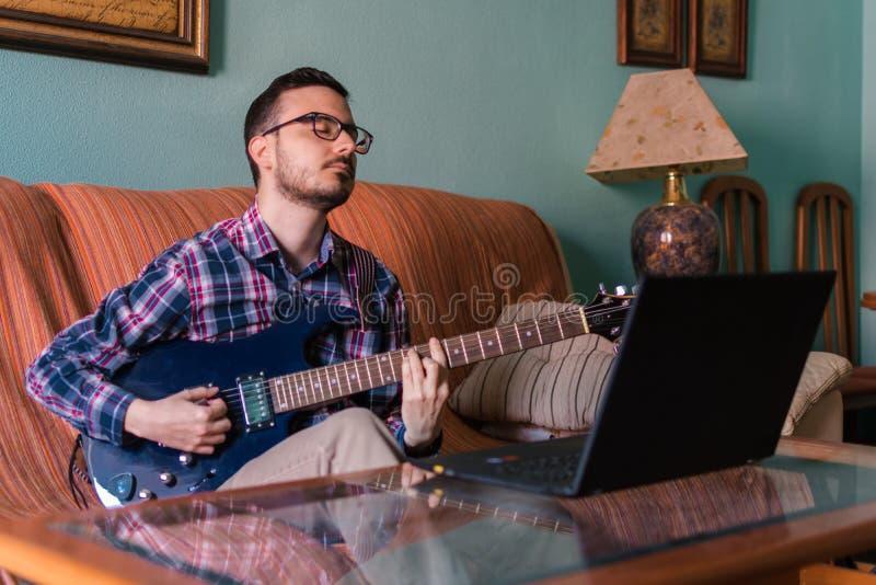 Mannen lär att spela den elektriska gitarren hemma royaltyfria bilder