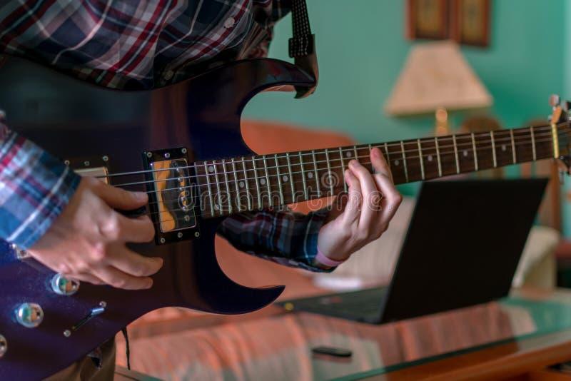 Mannen lär att spela den elektriska gitarren hemma arkivbilder