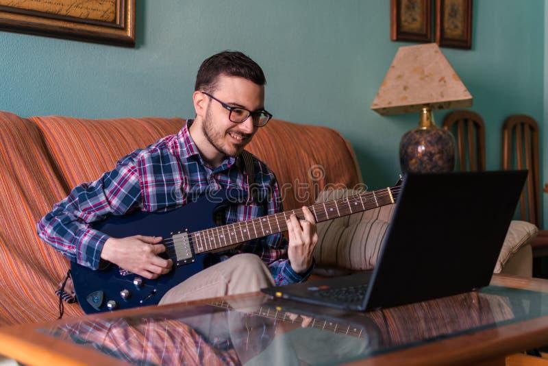 Mannen lär att spela den elektriska gitarren hemma royaltyfria foton