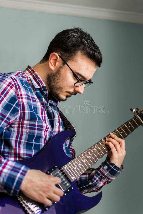 Mannen lär att spela den elektriska gitarren hemma royaltyfri fotografi