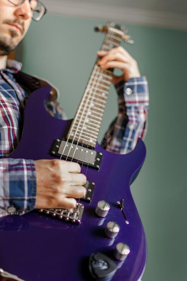 Mannen lär att spela den elektriska gitarren hemma royaltyfri foto