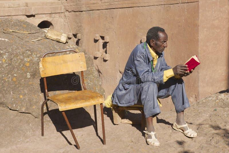 Mannen läser boken i Lalibela, Etiopien arkivbilder