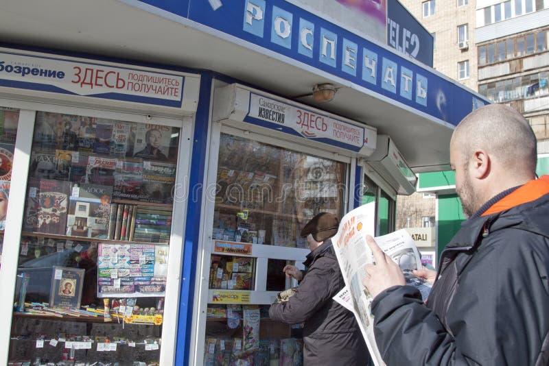 Mannen läser den ryska tidningen arkivfoton