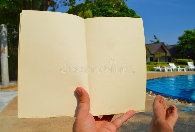Mannen läser en bok på semester arkivbilder