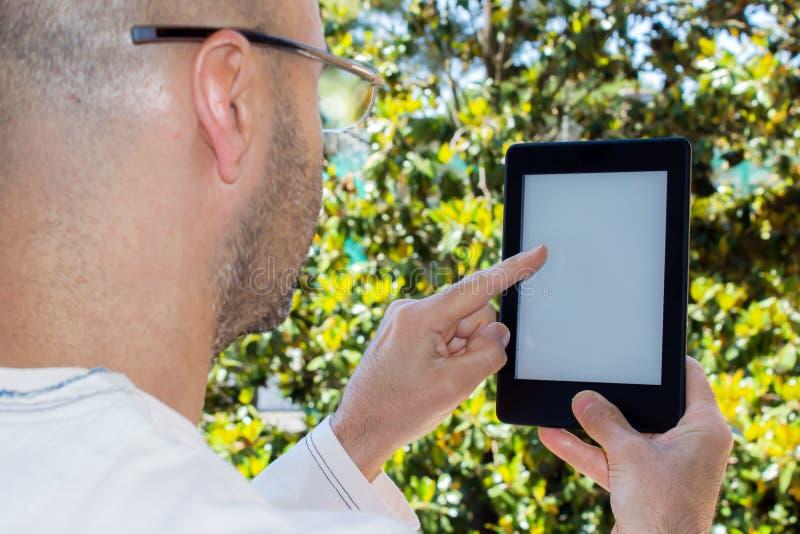 Mannen läser en eBook i en trädgård royaltyfri fotografi