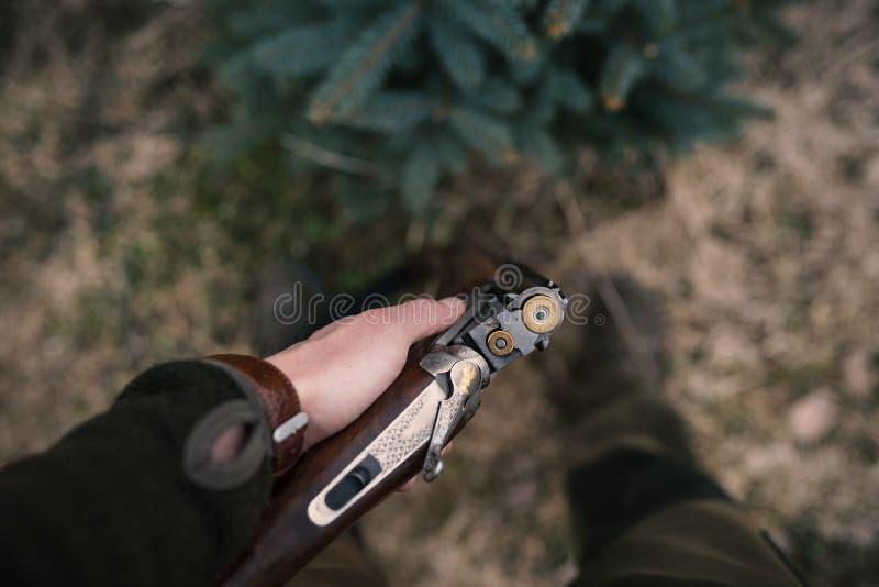 Mannen laddar hans jaga vapen Manliga jägare är klara för att jaga Detalj på geväret och ammunitions arkivfoton