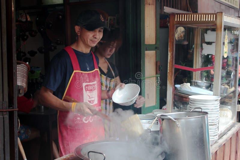 Mannen lagar mat den vanliga nudeln i Talad-Nam av Thailand fotografering för bildbyråer