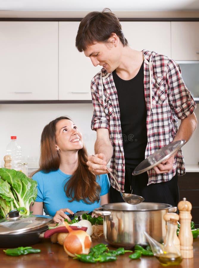 Mannen lagar mat mat för flickan arkivfoto