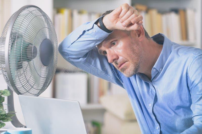 Mannen lider fr?n v?rme i kontoret eller hemma royaltyfri foto