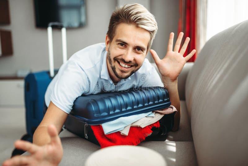 Mannen ligger på den överlastade resväskan, avgifter på resa royaltyfria bilder