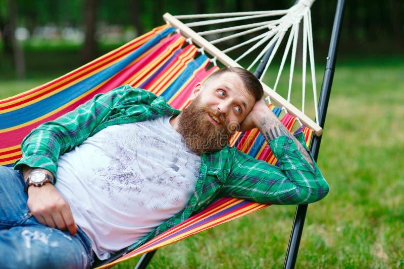 Mannen ligger på en hängmatta royaltyfria bilder