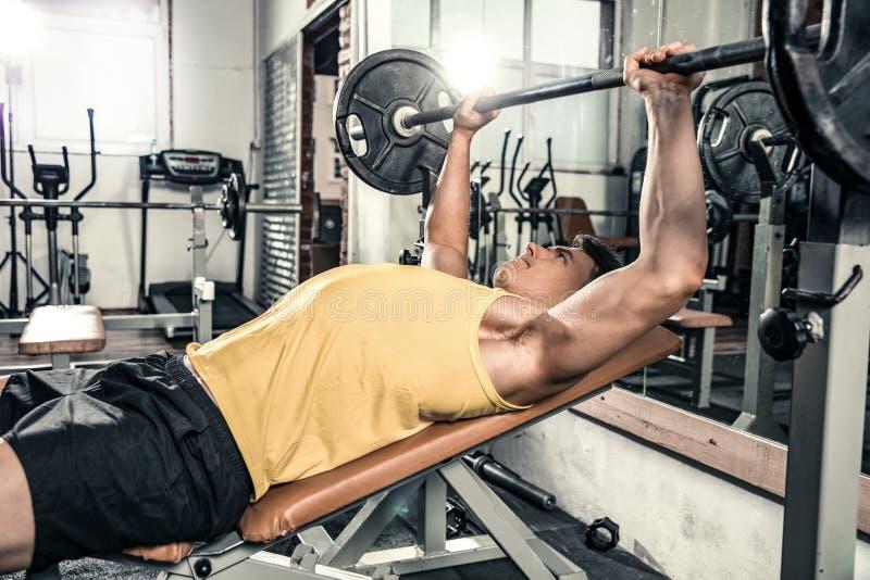 Mannen ligger på idrottshallbänken royaltyfri fotografi