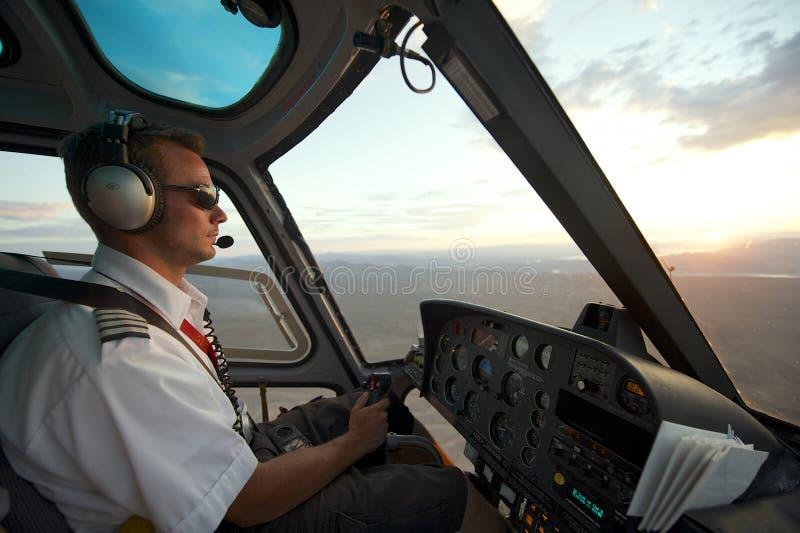 Mannen lotsar helikoptern till Grandet Canyon på solnedgången, circa Las Vegas, USA arkivfoton