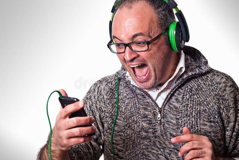 Mannen lyssnar musik på hörlurar och skri aloud arkivbilder