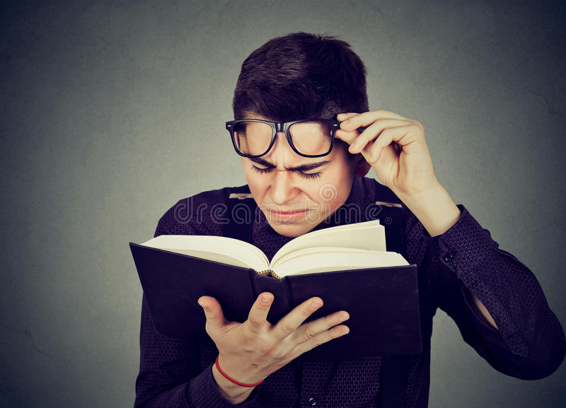 Mannen med ögonexponeringsglas som försöker att läsa boken, har siktproblem fotografering för bildbyråer