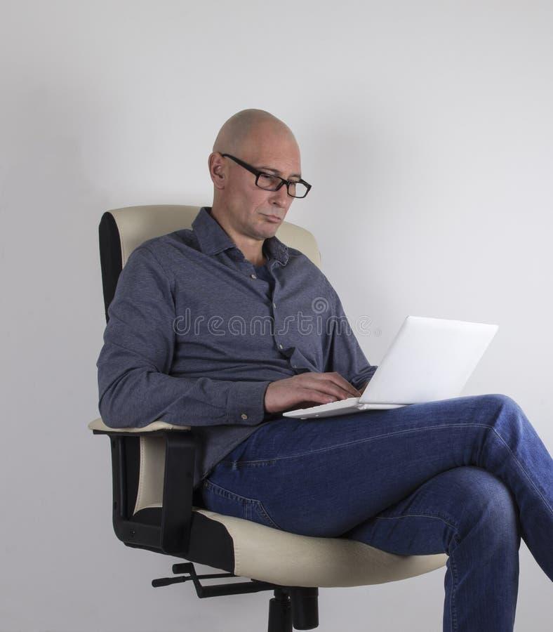 Mannen med bärbar datorsammanträde på stolen arkivfoton