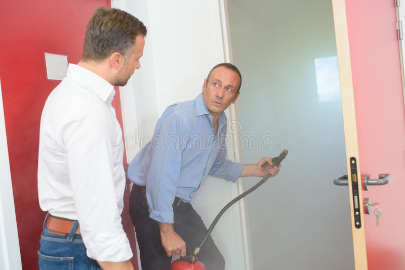 Mannen med brandsläckaren på dörröppningsrök fyllde rum royaltyfri foto