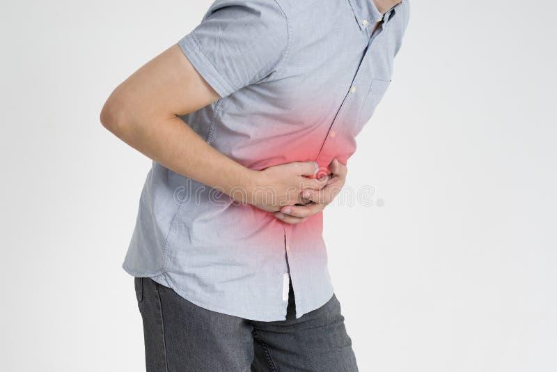 Mannen med buk- smärtar, mageknipet på grå bakgrund arkivfoto