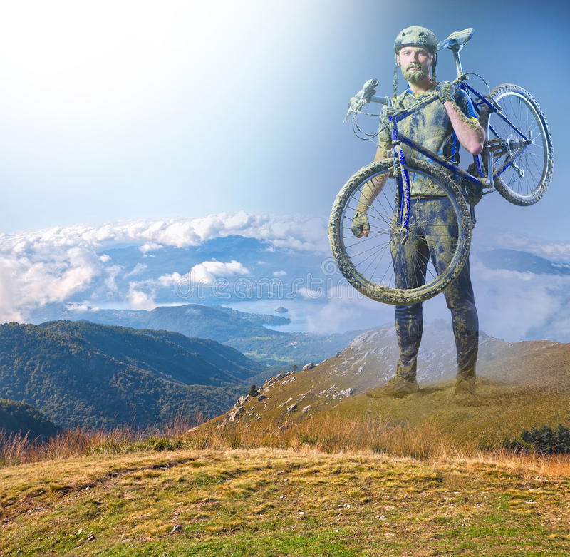 Mannen med cykeln i sandanseende på bergbakgrund collage royaltyfri fotografi