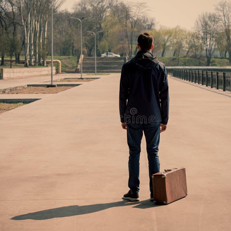 Mannen med den gamla resväskan ser in i avståndet royaltyfri foto