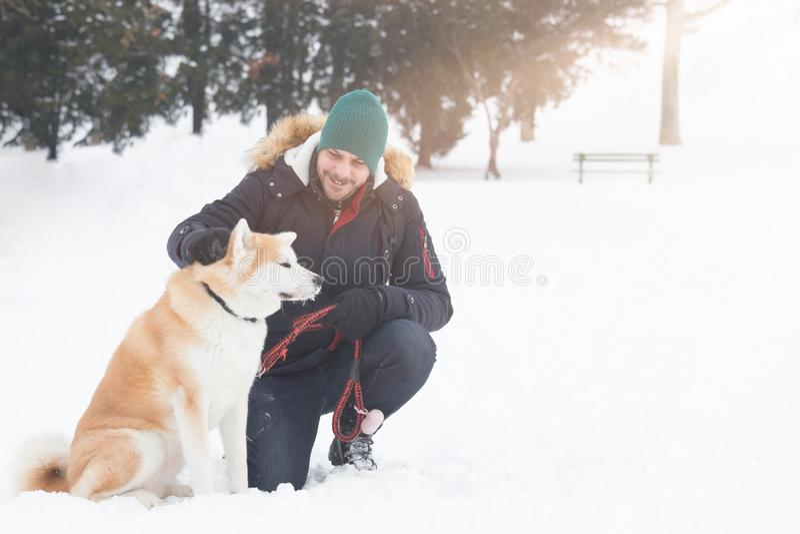 Mannen med det akita hundhusdjuret parkerar in på snöig dag slitage vit vinter för härlig stående för begreppsklänningflicka arkivfoton