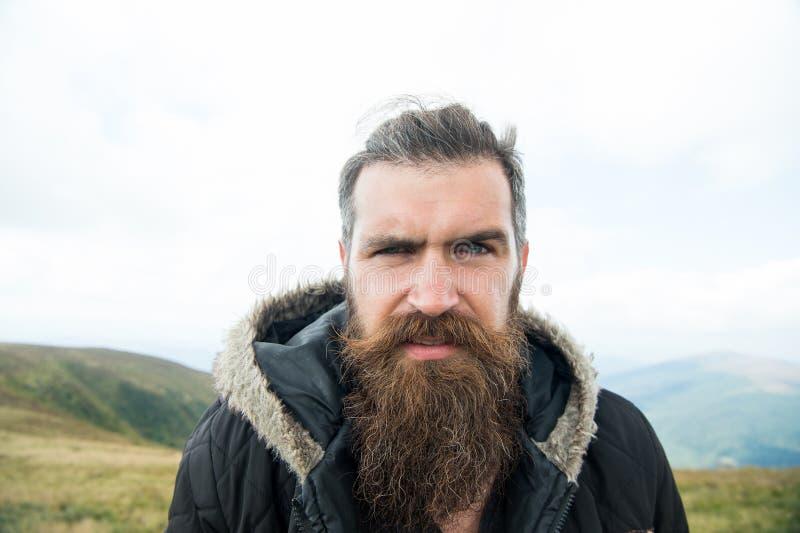 Mannen med det långa skägget och mustaschen bär omslaget Hipsteren på strikt framsida med skägget ser brutally, medan fotvandra e arkivbild