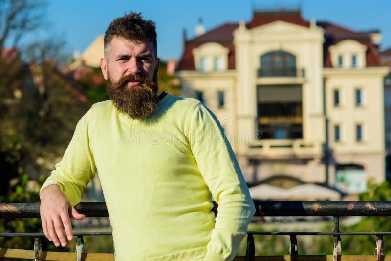 Mannen med det långa skägget tycker om sikt från balkong wrist för watch för avkoppling för begreppshandfack Den skäggiga mannen  arkivfoto