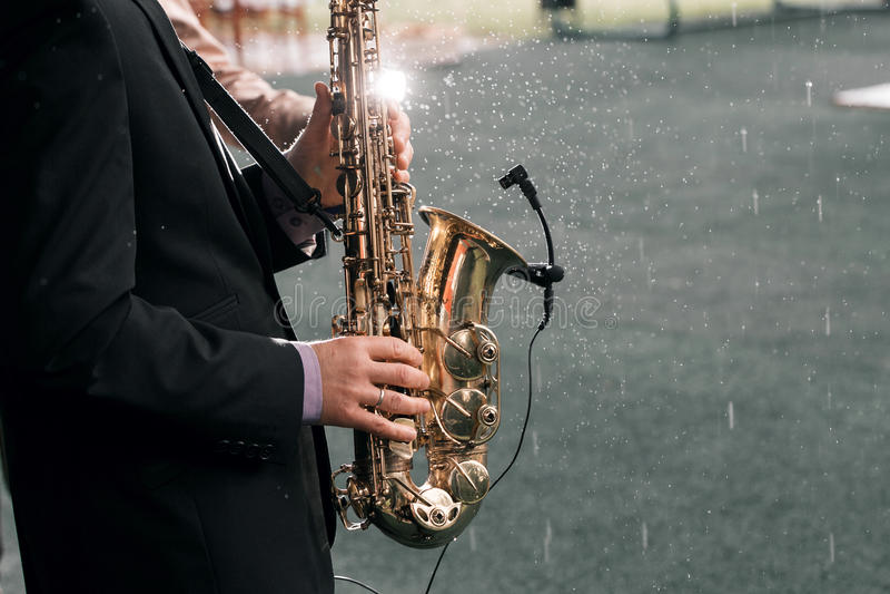 Mannen med en saxofon står under regn royaltyfria foton