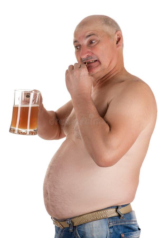 Mannen med en stor buk äter fisken med ett öl i hand arkivfoton