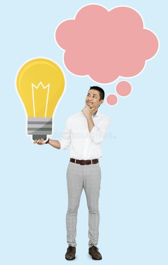 Mannen med en symbol för ljus kula och ett anförande bubblar arkivfoto