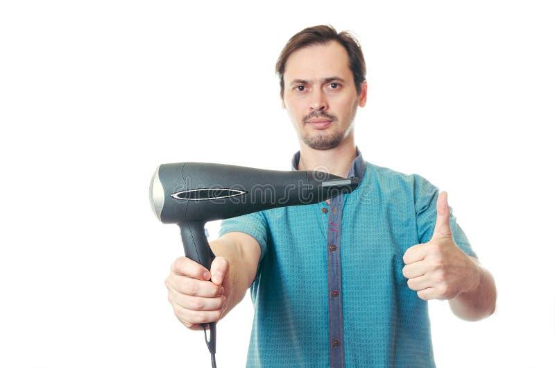 Mannen med ett skägg rymmer hårtorken i hand royaltyfria bilder