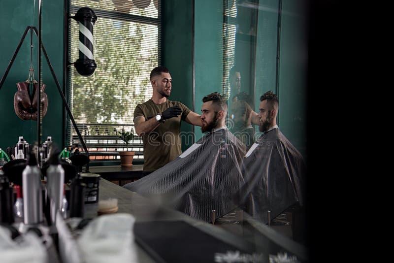 Mannen med ett skägg sitter i stolen, framme som spegeln på en barberare shoppar Barberaren gör en frisyr arkivbild