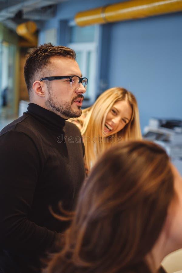 Mannen med exponeringsglas talar, och hans kollega skrattar royaltyfri bild