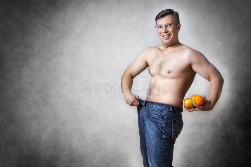 Mannen med frukter har borttappad kroppsvikt royaltyfri fotografi