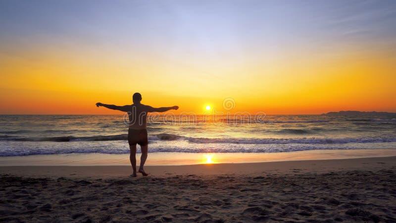 Mannen med händer som är öppna i SEGER, poserar vitt går på den tomma havstranden in i vatten arkivfoton