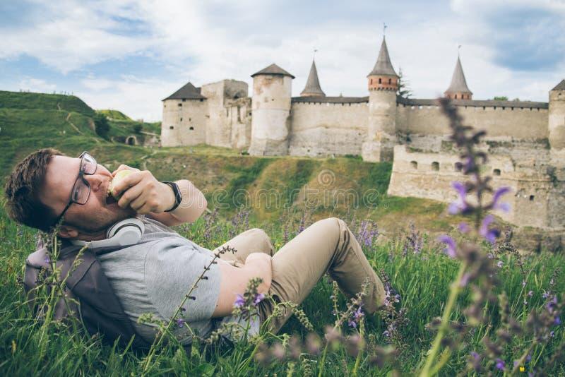 Mannen med hörluren ligger på jordningen och att se den gamla slotten och att äta ett äpple royaltyfria foton